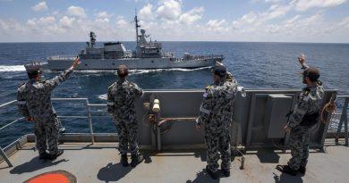 Members of HMAS Sirius' ship's company wave to the crew of Royal Malaysian Navy ship KD Lekir in the Andaman Sea. Photo by Leading Seaman Thomas Sawtell.