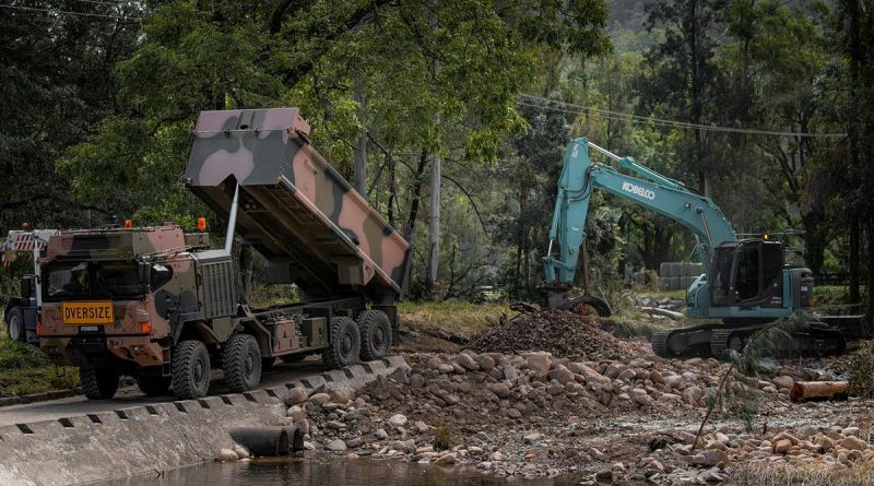An Army HX77 and excavator being used to reconstruct a bridge near Wauchope, NSW, which was damaged by the floods. Photo by Private Jacob Hilton.