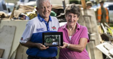 Alan and Janice Hunt stand in front of flood damaged possessions in Lower MacDonald, NSW. Photo by Corporal Sagi Biderman.