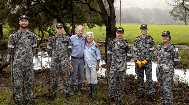 Sailors with Neil and Gwen Mcleod after clearing debris from their flood-damaged property in Scotts Head, NSW. Photo by Corporal Robert Whitmore.