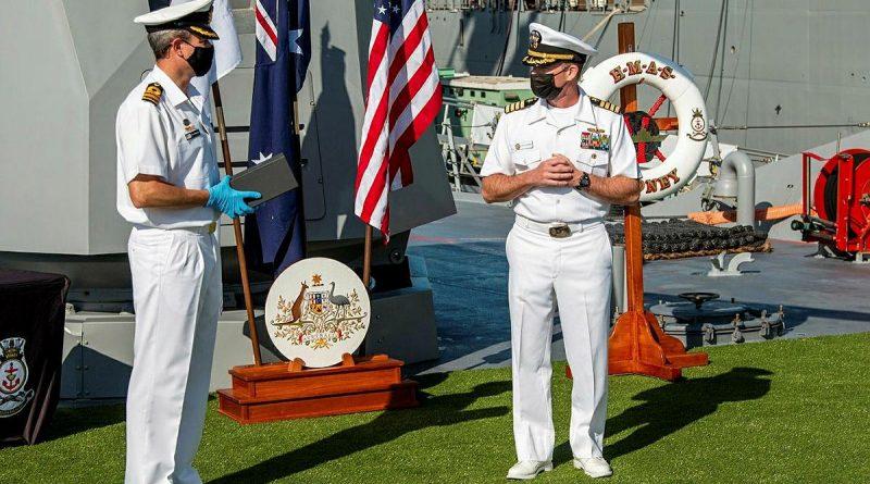 Commanding Officer HMAS Sydney Commander Ted Seymour, left, presents United States Navy officer Commander Robert Eilers with a Commander Australian Fleet Silver Commendation on board Sydney in San Diego. Story by Lieutenant Commander Scott MacPherson.