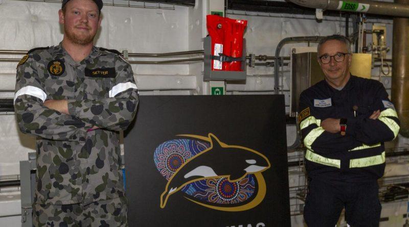 Leading Seaman Jackson Setter, left and Navantia Australia engineer Jose Luis Bouza Fernandez stand with a new passageway sign for HMAS Supply. Story by Lieutenant Jessica Craig. Photo by Able Seaman Benjamin Ricketts.