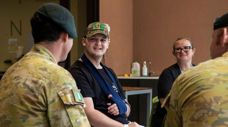 Corporal Brenton Munro, left, from the 6th Battalion, Royal Australian Regiment, talks with 14-year-old Knox Scott and his mother Lauren at Ronald McDonald House, South Brisbane. Photo by Corporal Nicole Dorrett.