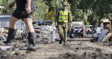 An Australian Army soldier deployed on Operation NSW Flood Assist walks between debris from flood damage in Wisemans Ferry, New South Wales. Photo by Corporal Sagi Biederman.