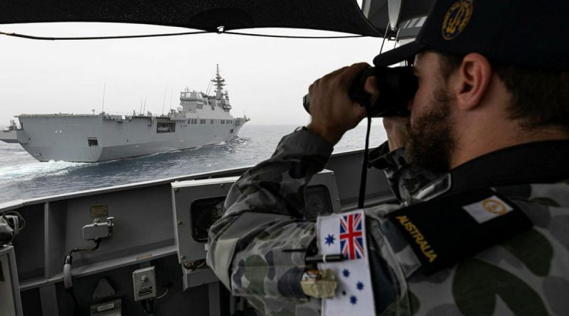 Midshipman Thomas Armstrong checks HMAS Parramatta's distance from Japan Maritime Self-Defense Force vessel JS Ise with laser range-finding binoculars during Exercise ARC21. Story and photo by Leading Seaman Jarrod Mulvihill.