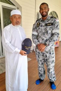Able Seaman Boatswains Mate Ebrahim Dollie presents the Imam of Cocos Keeling Islands Mosque with an HMAS Glenelg ball cap, representing the ship in which he serves. Photo by Lance Corporal Flannagan.
