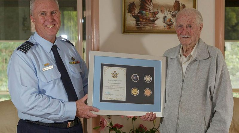 Senior Australian Defence Force Officer for RAAF Base Williamtown Group Captain Anthony Stainton presents George Lincoln an Air Force centenary memento. Story by Wing Commander Sue Yates. Photo by Sergeant David Gibbs.
