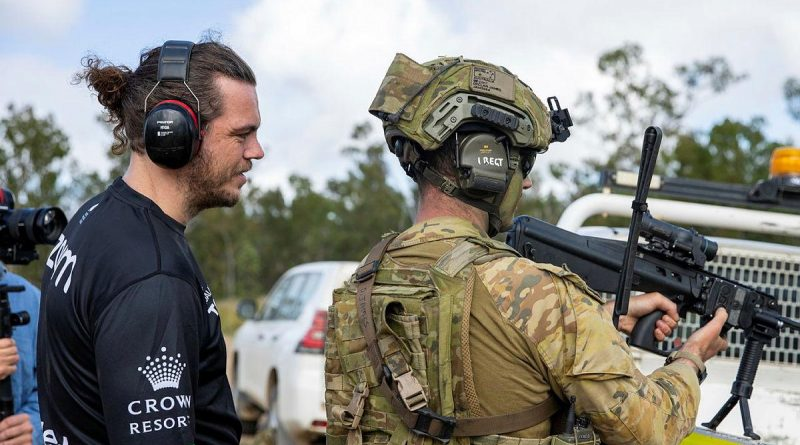 Captain Declan James explains the workings of an EF88 Austeyr Rifle to former South Sydney Rabbitoh player Ethan Lowe during his visit to Shoalwater Bay Training Area, Queensland. Story by Captain Jesse Robilliard. Photo by Corporal Nicole Dorrett.