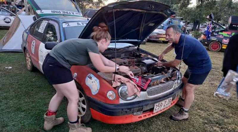 Major Lee Sankey and his daughter, Lydia, make some quick repairs to their vehicle during some down time in the Shitbox Rally.
