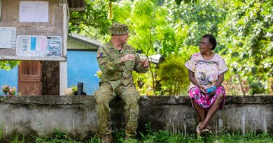 Captain Tim McPhee discusses the Vanuatu Government National Emergency Radio Network with Kerembei local Anika Bani during instillation. Photo by Corporal Olivia Cameron.