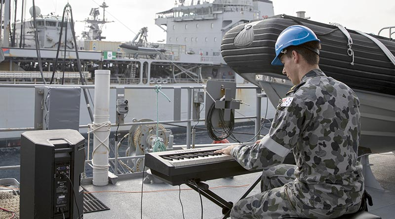 Able Seaman Xavier Riddell plays a tune for HMAS Sirius during a replenishment at sea in the Bay of Bengal. Photo by Leading Seaman Thomas Sawtell.