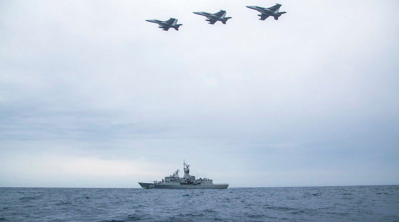 Three United States Navy EA-18G Growlers from VAQ-132 Squadron in formation over HMAS Ballarat in a Cooperative Activity during the ship's Regional Presence Deployment. Story by Lieutenant Gary McHugh. Photo by Leading Seaman Ernesto Sanchez.