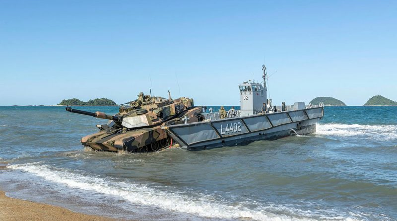 An Australian Army M1A1 Abrams Tank is loaded onto a Royal Australian Navy light landing craft, during Exercise Sea Explorer, Cowley Beach, Queensland. Story by Photo by Leading Aircraftwoman Jacqueline Forrester.