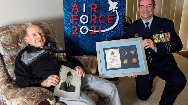 Senior ADF Officer RAAF Base Amberley Group Captain Iain Carty presents Air Force veteran Bill Heatherill with an Air Force 2021 commemorative memento in celebration of his 100th birthday. Story by Evita Ryan. Photo by Corporal Jesse Kane.
