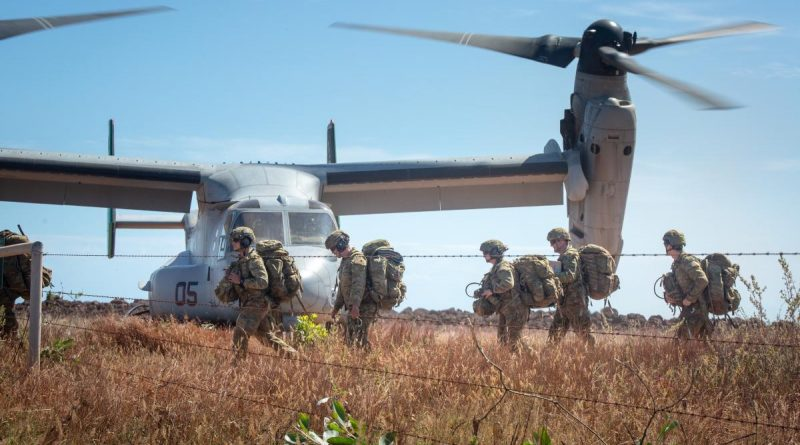 Australian Army soldiers carry their gear off a landing zone during Exercise Crocodile Response at Point Fawcett, Northern Territory. Story byLieutenant Gordon Carr-Gregg.