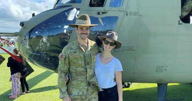 Lance Corporal Brendan Cox and his partner, Holly Fowler, stand in front of an Australian Army CH47F Chinook helicopter.