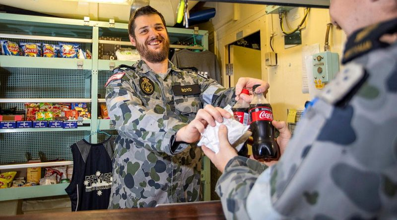 HMAS Ballarat's Assistant Canteen Manager Leading Seaman Timothy Boyd serves Able Seaman Daniel Johnson during deployment. Story by Lieutenant Geoff Long. Photo by Leading Seaman Ernesto Sanchez.