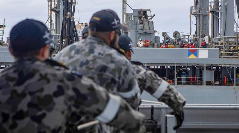 HMAS Ballarat's Ship's Company heave in a messenger line during a replenishment at sea with USNS Big Horn. Story by Lieutenant Gary McHugh. Photo by Leading Seaman Ernesto Sanchez.