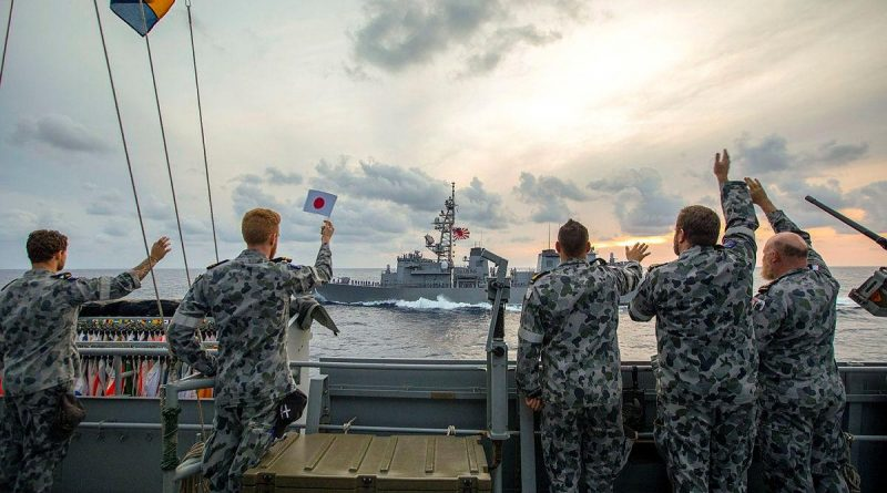 HMAS Ballarat's ship's company wave farewell as Japan Maritime Self-Defense Force Ship Murasame passes by after completing training together. Story by Lieutenant Gary McHugh. Photo by Leading Seaman Ernesto Sanchez.