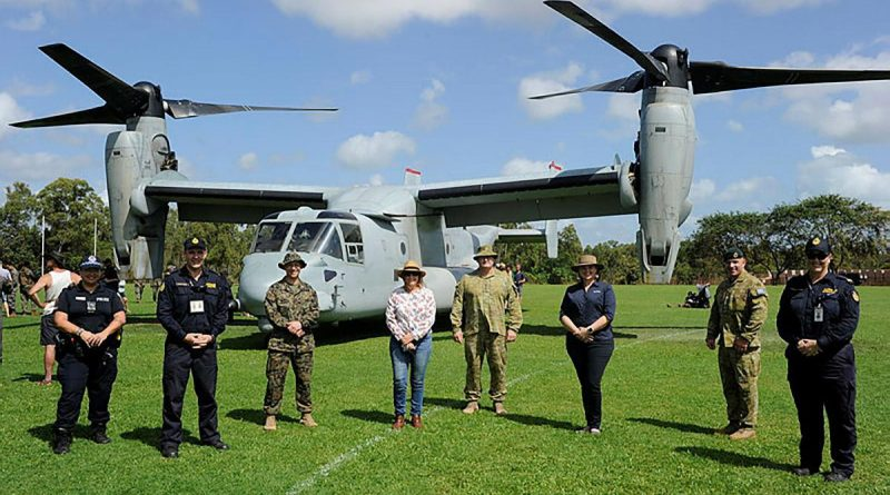 Community leaders and representatives from the NT Police and Australian Border Force stand with ADF and US Marine Corps members in front of an MV-22B Osprey. Story by Lieutenant Gordon Carr-Greg.