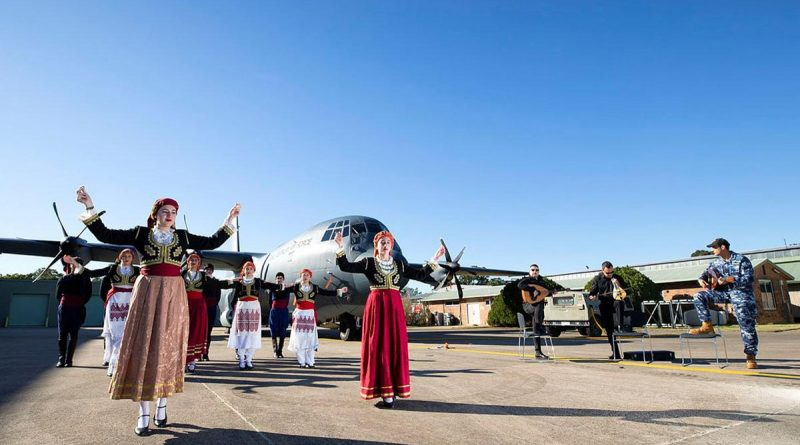 Dancers from the Cretan Association of Sydney perform in front of a C-130J Hercules as No. 37 Squadron avionics technician Leading Aircraftman Yianni Skoulakis, right, plays the laouto at RAAF Base Richmond. Story by Eamon Hamilton. Photo by Corporal David Said.