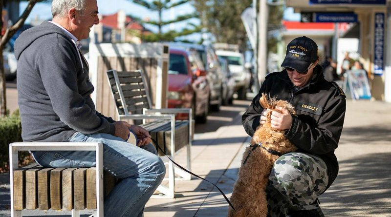 Able Seaman Tegan Bradley pats an Eden resident's dog during the ship's company's walk into the NSW town during a port visit. Story by Acting Sub Lieutenant Jack Meadows. Photo by Leading Seaman Daniel Goodman.