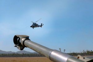 An Australian Army Tiger Armed Reconnaissance Helicopter flies past an M777 Howitzer at Shoalwater Bay Training Area, Talisman Sabre 2021. Photo by Warrant Officer Class 2 Max Bree.