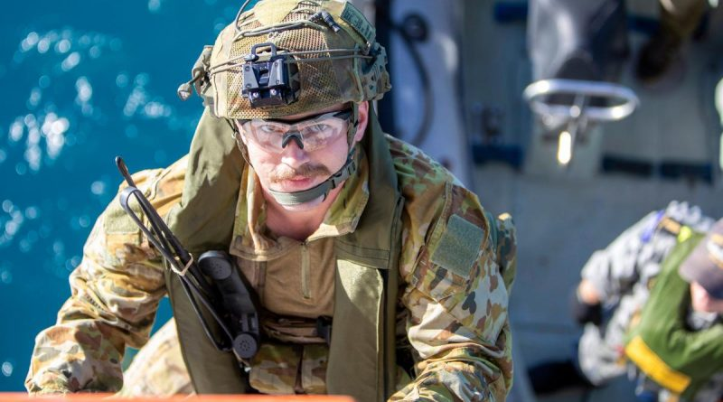 An Australian Army soldier climbs aboard HMAS Ballarat from a Rigid-Hulled Inflatable Boat during joint pre-landing force training, off the coast of Queensland, during Exercise Talisman Sabre 2021. Story by Lieutenant Commander Ryan Zerbe. Photo by LSIS Ernesto Sanchez.