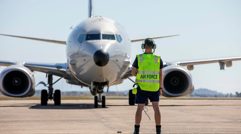 A Royal Australian Air Force Avionics Technician guides a P-8A Poseidon aircraft into position, as it prepares to depart RAAF Base Townsville in Queensland. Story by Flight Lieutenant Chloe Stevenson. Photo by Leading Aircraftwoman Emma Schwenke.