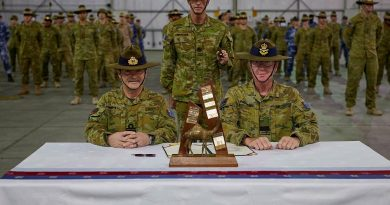Rear Admiral Michael Rothwell, left, and Air Commodore David Paddison, right, after signing the Transfer of Authority for Command of Joint Task Force 633, witnessed by Warrant Officer Class One Mark Retallick. Photo by Sergeant Andrew Sleeman.