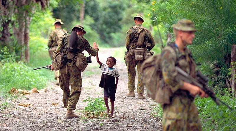 Boy greets Aussie soldiers on patrol in East Timor, Photo by Corporal Brian Hartigan.