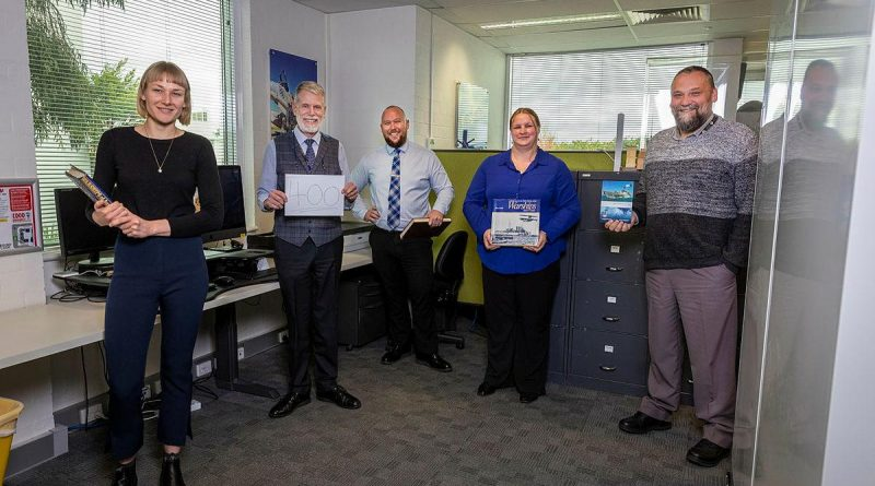 Naval History Section staff Honae Cuffe, Director John Perryman, Rob Garratt, Simone Alferink and Petar Djokovic celebrate the publication of their 400th ship history at their offices in Fyshwick, Canberra. Story and photo by Sergeant Sebastian Beurich.