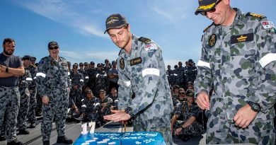 Commanding Officer Ballarat Commander Antony Pisani, right, with the youngest crew member Seaman Christiaan Rijkaart during the cutting of the ship's birthday cake at sea. Story by Lieutenant Gary McHugh. Photo by Leading Seaman Ernesto Sanchez.