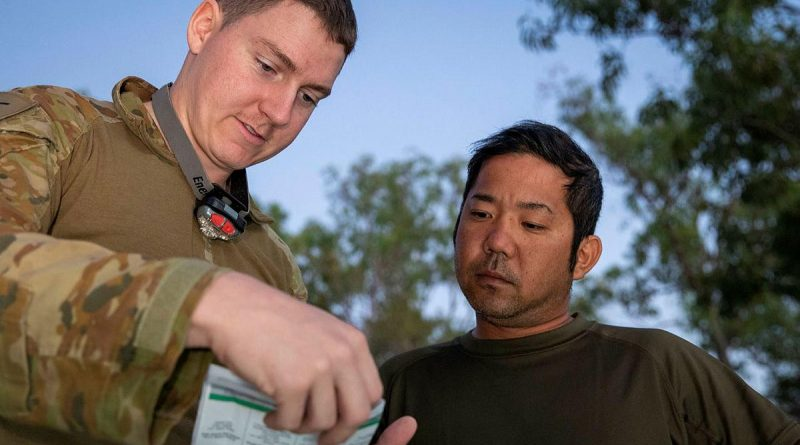 Army linguist Lance Corporal Cameron Murdoch talks with Japan Ground Self-Defense Force soldier Sergeant First Class Shigeyuki Azuma during Exercise Southern Jackaroo. Story and photo by Private Jacob Joseph.