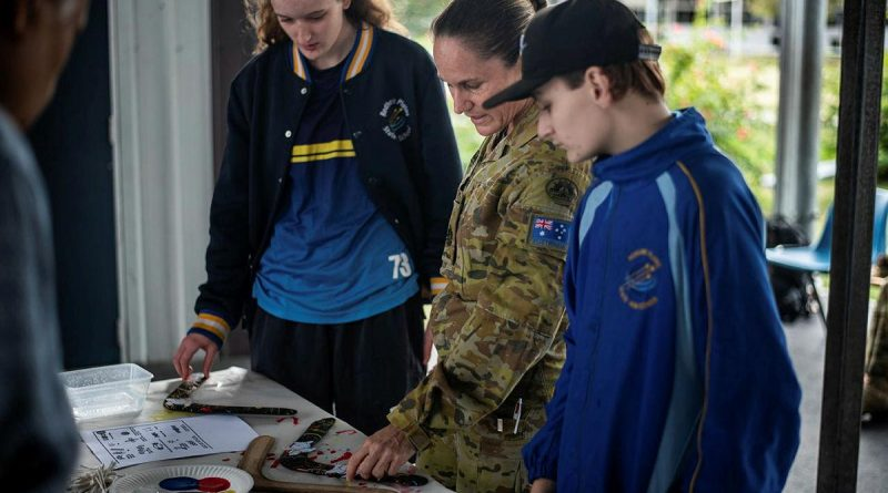 Warrant Officer Class One Kelly Hammant instructs students from Redbank Plains State High School how to paint boomerangs in traditional styles. Story by Captain Jesse Robilliard. Photo by Private Jacob Hilton.
