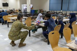 Camp Commandant, Major Joel Bell gives a ball to an evacuee in the mess hall of the temporary camp, in Australia's main operating base in the Middle East. Photo by Leading Aircraftwoman Jacqueline Forrester.