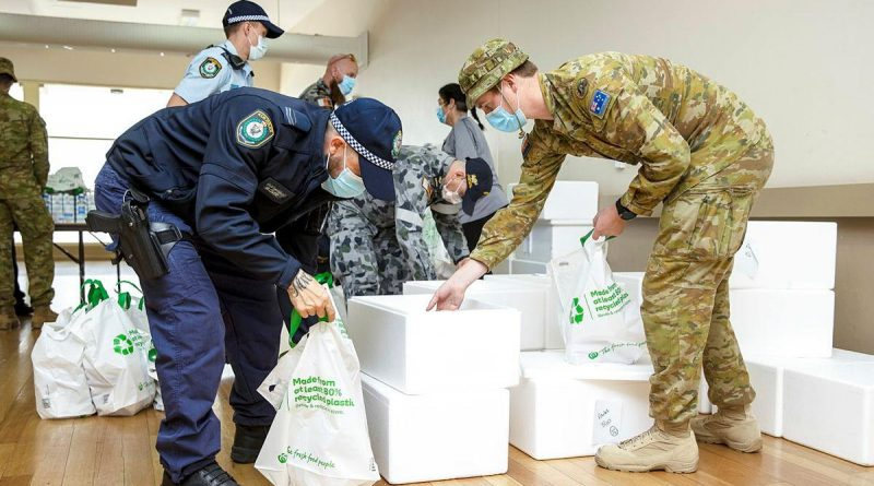 NSW Police and ADF members prepare to deliver pre-made meals as part of care packages given to homes in the Fairfield community in Sydney. Story by Lieutenant Commander John Thompson. Photo by Corporal Dustin Anderson.