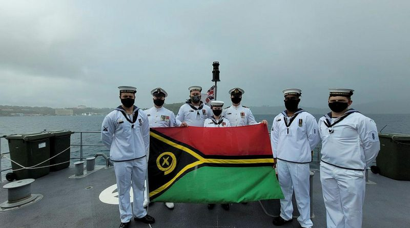 Personnel from HMAS Glenelg, with Commanding Officer Lieutenant Commander Alexander Finnis, third from right, display the Vanuatu flag while at anchor at Port Vila during Vanuatu's Independence Day celebrations. Story by Lieutenant Sarah Rohweder.