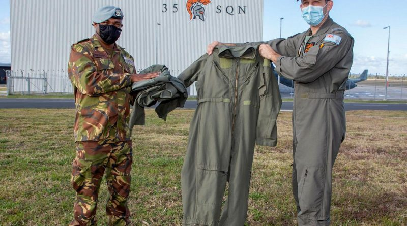 Captain Randall Hepota of the Papua New Guinea Defence Force is presented with flying clothing during his visit to No. 35 Squadron at RAAF Base Amberley by Squadron Leader Robert Crawford. Story by Flight Lieutenant Clarice Hurren. Photo by Sergeant Peter Borys.