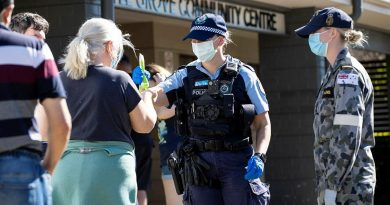 NSW Police Constable Megan Green and Seaman Jordan Parsons hand out sunscreen to civilians waiting in line for a COVID-19 test at the Wattle Grove Community Centre. Story by Lieutenant Commander John Thompson. Photo by Corporal Dustin Anderson.