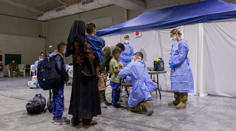 An Australian Defence Force medic assesses a child in the evacuee handling centre at Australia's main operating base in the Middle East. Story by Lieutenant Max Logan. Photo by Leading Aircraftwoman Jacqueline Forrester.