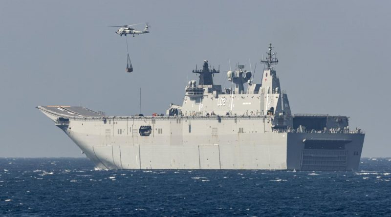HMAS Anzac's embarked MH-60R collects a desalination plant from HMAS Canberra for delivery to the Balinese island of Nusa Lembongan during IPE21. Photo by Leading Seaman Leo Baumgartner.