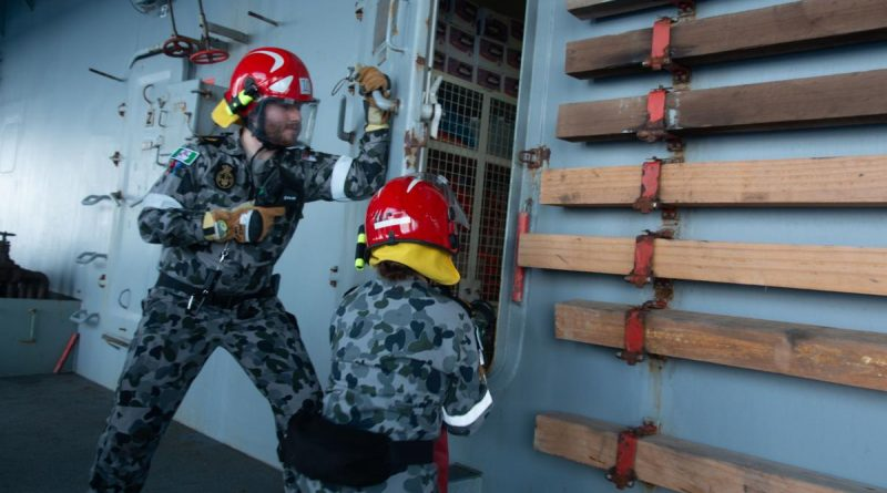 Able Seaman Paul Murra and Able Seaman Lydia Monk participate in a fire hose drill during damage control training on board HMAS Sirius. Story by Lieutenant Commander Ric Mingramm.