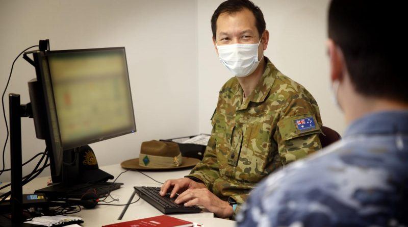 Major Timothy Chan, Officer Commanding Bravo Company, Joint Task Force 629.1.1, works with a member of the task force at HMAS Kuttabul, Sydney. This image has been digitally altered. Photo by Aircraftwoman Kate Czerny.