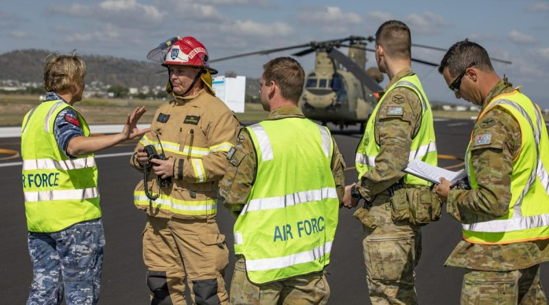 Medical officer Flight Lieutenant Melanie Smyth gives the fire commander from Aviation Rescue Fire Fighting Services and fellow Air Force members a situation report on the crash victims. Story by Flying Officer Robert Hodgson. Photo by Corporal Jesse Kane.
