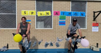 Petty Officer Simon Taylor, left, and Lieutenant Commander James Knight compete in the HMAS Watson spin-a-thon fundraiser for Dry July. Story by Lieutenant Kiz Welling-Burtenshaw.